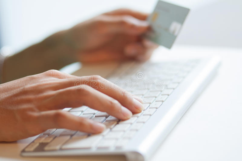 Δακτυλογράφηση ενός πληκτρολογίου και κράτημα μιας πιστωτικής κάρτας για on-line να ψωνίσει στοκ φωτογραφία με δικαίωμα ελεύθερης χρήσης