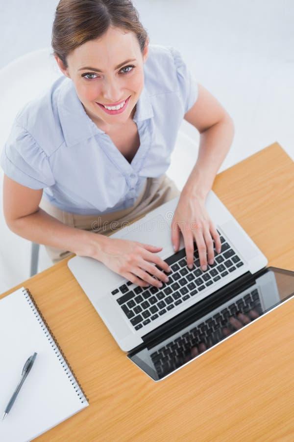 Δακτυλογράφηση επιχειρηματιών στο lap-top της και χαμόγελο επάνω στη κάμερα στοκ εικόνα με δικαίωμα ελεύθερης χρήσης