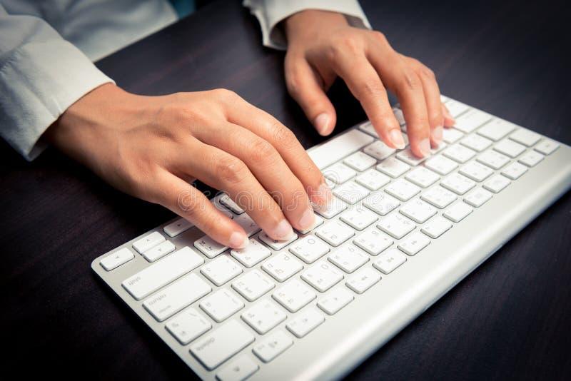 Δακτυλογράφηση χεριών γυναίκας στο πληκτρολόγιο υπολογιστών στοκ φωτογραφία