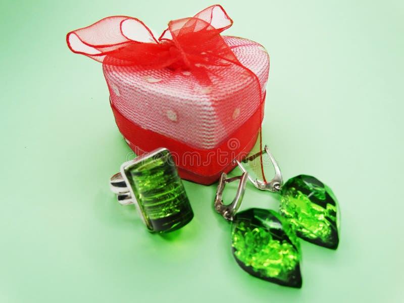 Δαχτυλίδι και σκουλαρίκια κοσμήματος με τα φωτεινά σμαραγδένια κρύσταλλα πολύτιμων λίθων στοκ εικόνες με δικαίωμα ελεύθερης χρήσης