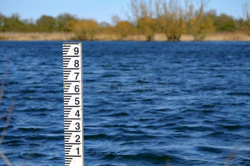 Δείκτης ύψους παλίρροιας που βλέπει μερικώς καταδυμένος σε έναν παλιρροιακό ποταμό στοκ εικόνες