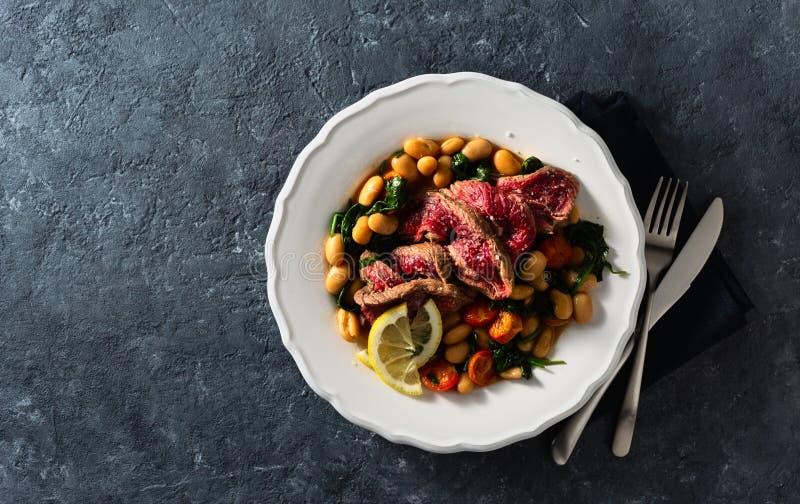 Δείπνο με μπριζόλα βοδινού με λευκά φασόλια, σπανάκι και ντομάτες σκούρο πέτρινο φόντο με φωτοτυπικό χώρο στοκ φωτογραφία