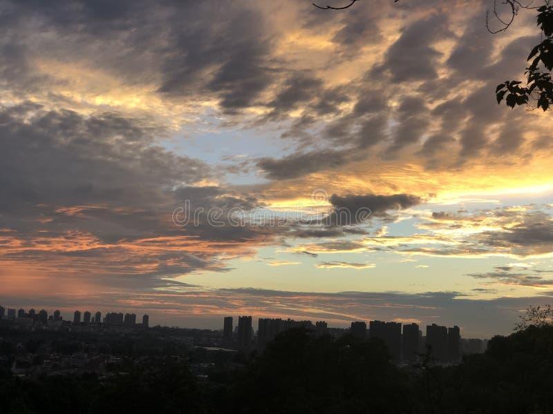 Δεδομένου ότι τα σύνολα ήλιων, ο χρυσός ήλιος λάμπουν στα άσπρα σύννεφα στοκ εικόνες