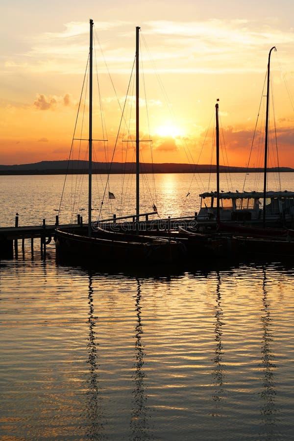 Δεμένες sailboat βάρκες στο ηλιοβασίλεμα πέρα από τη λίμνη Steinhuder Meer στη Γερμανία στοκ εικόνες