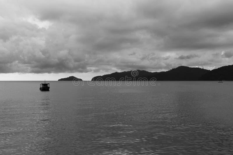Δεμένος βάρκα σκοτεινός ουρανός νησιών Θαλασσών της Νότιας Κίνας απόμακρος μονοχρωματικός στοκ φωτογραφία με δικαίωμα ελεύθερης χρήσης