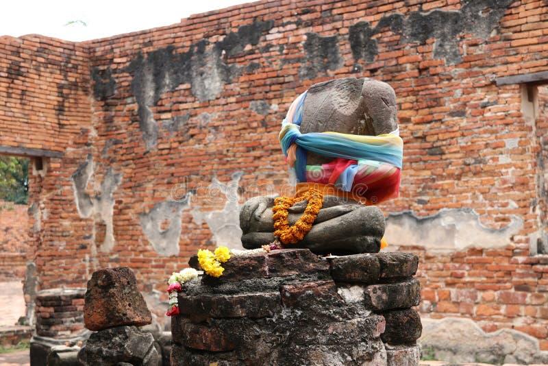 Δεν υπάρχει κανένας επικεφαλής, ελλιπής της αρχαίας πέτρας Βούδας και της λατρείας από το ζωηρόχρωμα ύφασμα και το λουλούδι στις  στοκ φωτογραφία