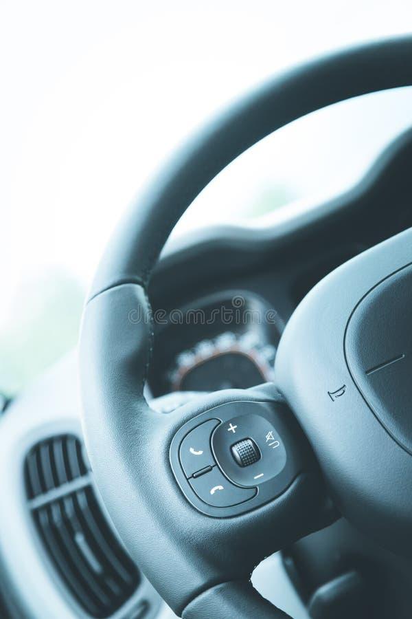Δερμάτινος-μαύρο τιμόνι με τον τηλεχειρισμό, σύγχρονο αυτοκίνητο, μουτζουρωμένο ταμπλό στοκ φωτογραφία με δικαίωμα ελεύθερης χρήσης