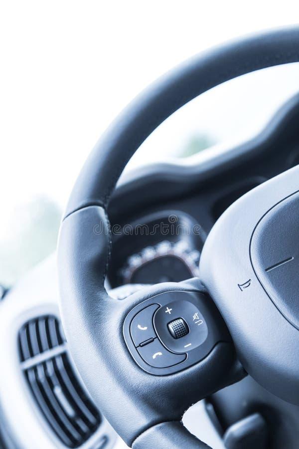 Δερμάτινος-μαύρο τιμόνι με τον τηλεχειρισμό, σύγχρονο αυτοκίνητο, μουτζουρωμένο ταμπλό στοκ φωτογραφία