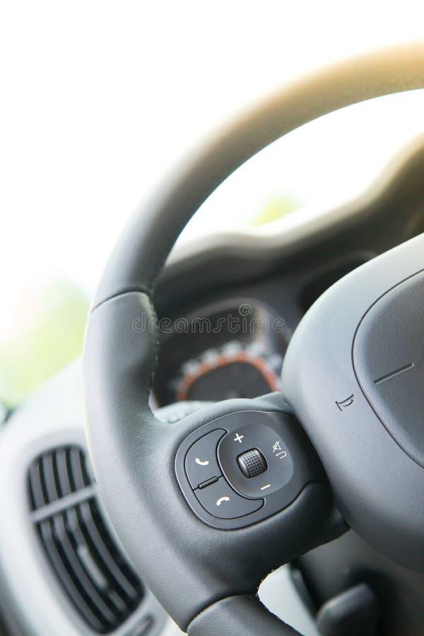 Δερμάτινος-μαύρο τιμόνι με τον τηλεχειρισμό, σύγχρονο αυτοκίνητο, μουτζουρωμένο ταμπλό στοκ φωτογραφίες με δικαίωμα ελεύθερης χρήσης