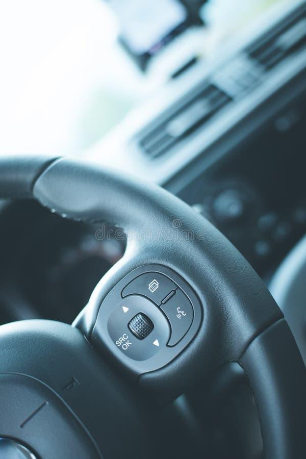 Δερμάτινος-μαύρο τιμόνι με τον τηλεχειρισμό, σύγχρονο αυτοκίνητο, μουτζουρωμένο ταμπλό στοκ εικόνα με δικαίωμα ελεύθερης χρήσης