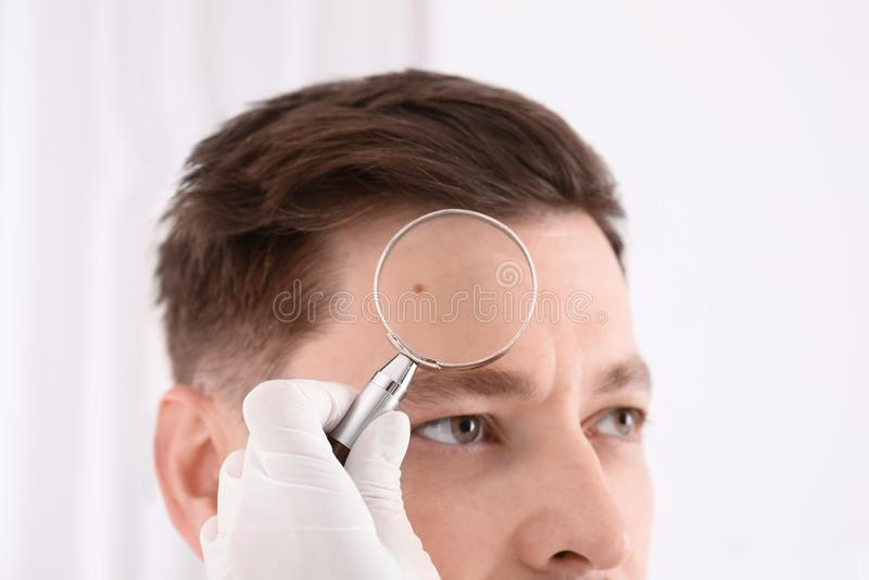 Δερματολόγος που εξετάζει τον ασθενή με την ενίσχυση - γυαλί στην κλινική στοκ φωτογραφία