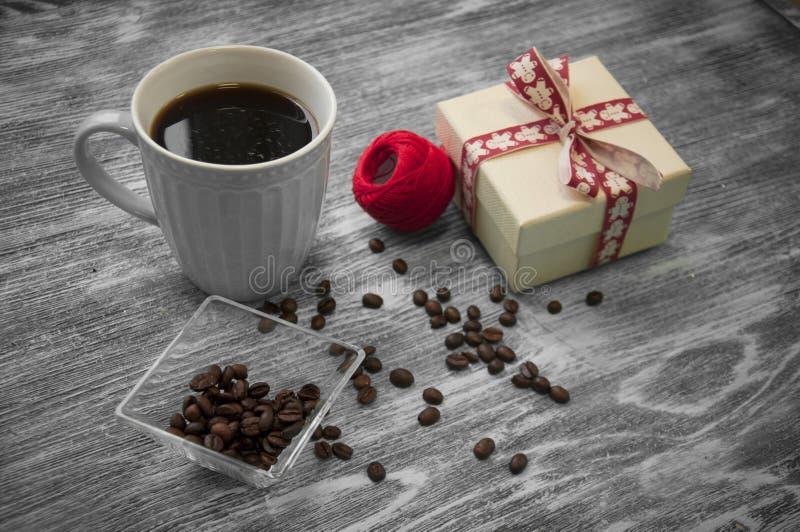 Δεσμίδα των νημάτων, του κιβωτίου δώρων, των φασολιών καφέ και του φλυτζανιού του cofee σε γκρίζο στοκ εικόνες
