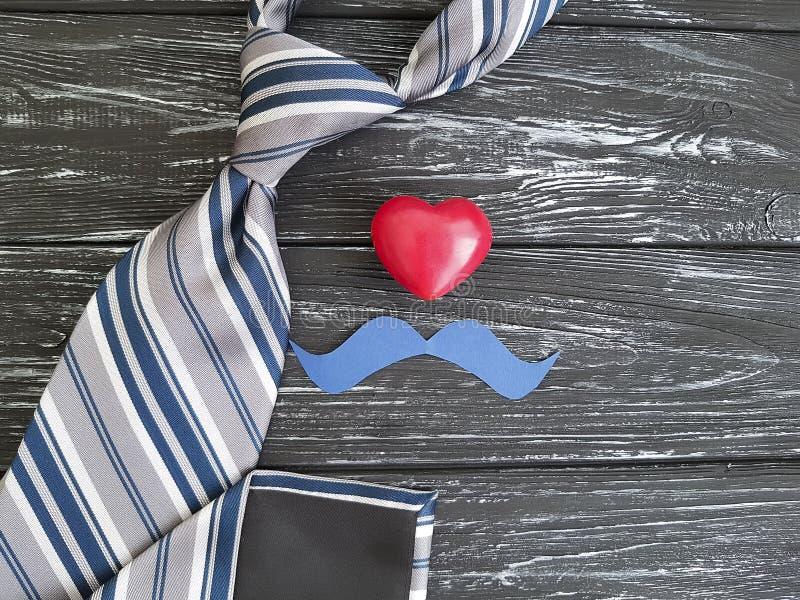 Δεσμός, καρδιά, εκλεκτής ποιότητας εορταστικό, παλαιό μαύρο ξύλινο υπόβαθρο ιδέας εγγράφου mustache στοκ φωτογραφία με δικαίωμα ελεύθερης χρήσης