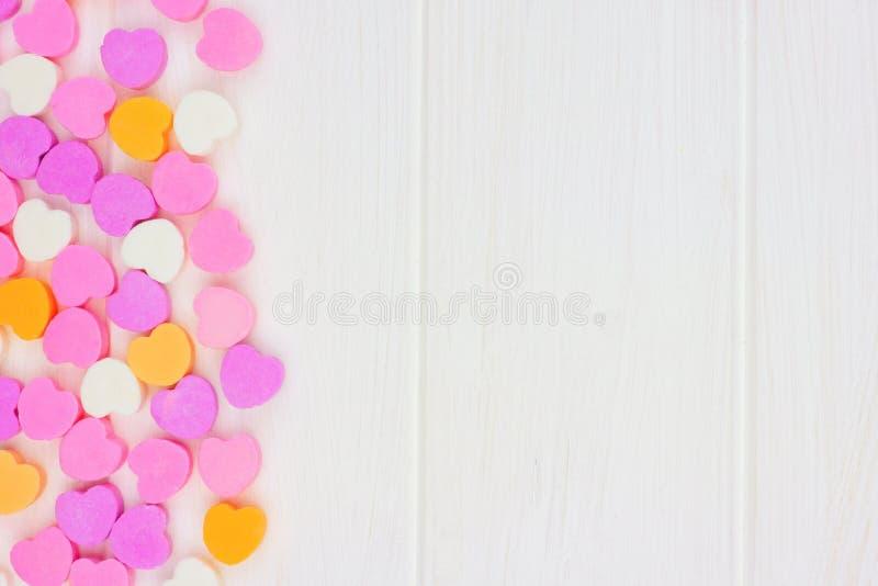 Δευτερεύοντα σύνορα καρδιών καραμελών ημέρας βαλεντίνων πέρα από το άσπρο ξύλο στοκ εικόνες