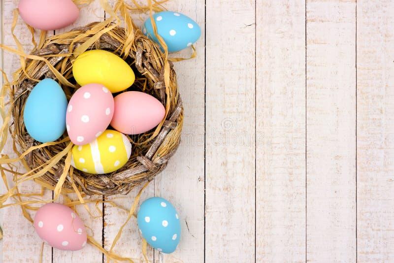 Δευτερεύοντα σύνορα φωλιών με τα ρόδινα, κίτρινα & μπλε αυγά Πάσχας ενάντια στο άσπρο ξύλο στοκ φωτογραφίες
