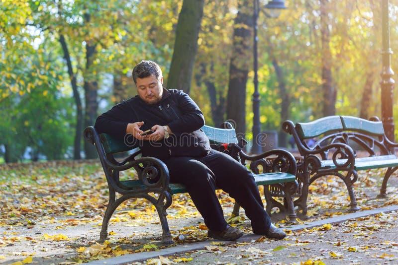 Δευτερεύον πορτρέτο της ευτυχούς συνεδρίασης ατόμων στον πάγκο πάρκων με το κινητό τηλέφωνο στοκ φωτογραφία με δικαίωμα ελεύθερης χρήσης