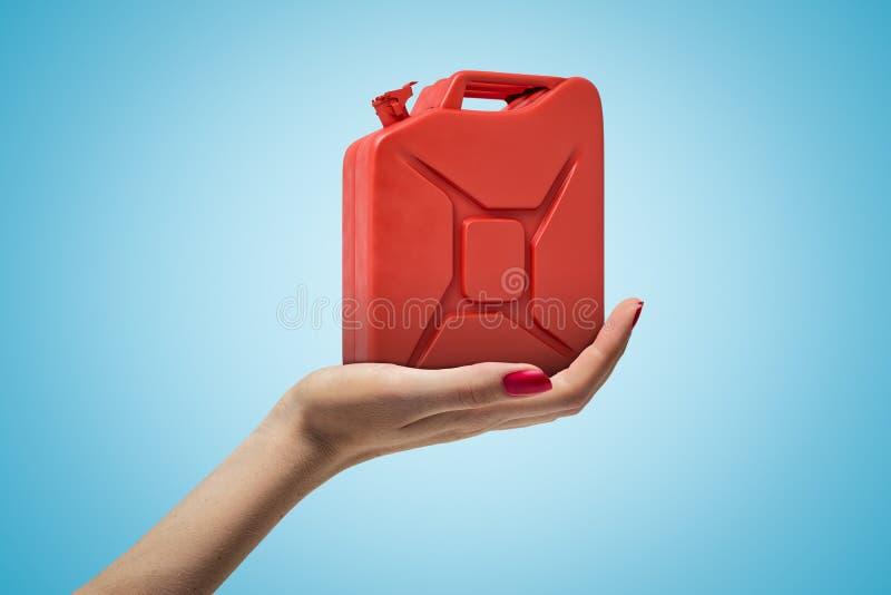 Δευτερεύουσα κινηματογράφηση σε πρώτο πλάνο του χεριού της γυναίκας που αντιμετωπίζει επάνω και που κρατά το κόκκινο μέταλλο jerr ελεύθερη απεικόνιση δικαιώματος