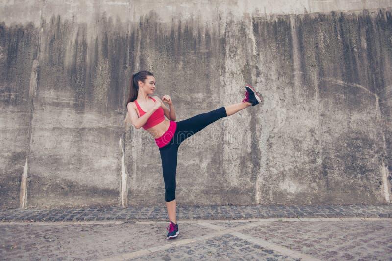 Δευτερεύουσα φωτογραφία σχεδιαγράμματος του ελκυστικού brunette, kickboxing υψηλό λάκτισμα στοκ εικόνες