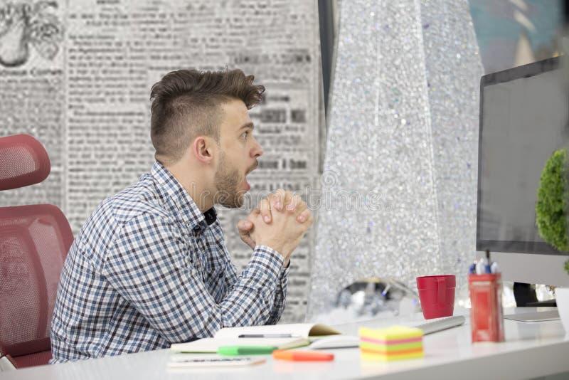Δευτερεύων πυροβολισμός σχεδιαγράμματος του ματαιωμένου νέου brunet επιχειρηματία, που φωνάζει στο lap-top του στην αρχή και τους στοκ εικόνα με δικαίωμα ελεύθερης χρήσης