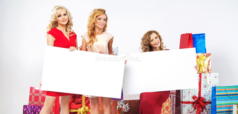 Δελεαστικές κυρίες που κρατούν τον κενό πίνακα διαφημίσεων στοκ εικόνες με δικαίωμα ελεύθερης χρήσης