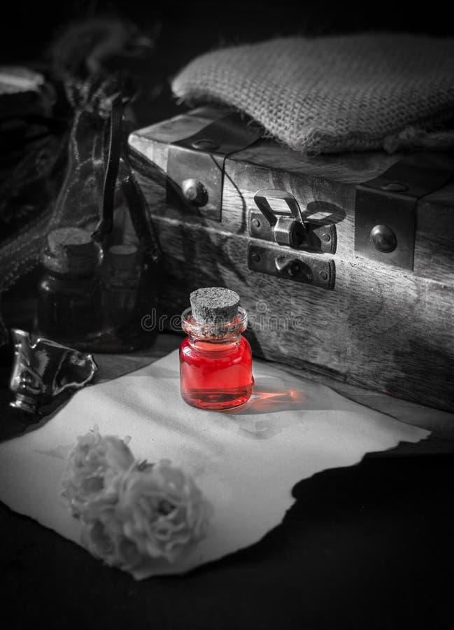 Δηλητήριο αγάπης, κόκκινο ποτό στο μπουκάλι η έννοια απομόνωσε το μαγικό λευκό στοκ φωτογραφίες