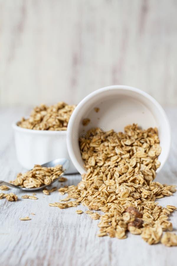 Δημητριακά προγευμάτων αμυγδάλων Granola που ανατρέπουν από το άσπρο κύπελλο στοκ εικόνες με δικαίωμα ελεύθερης χρήσης