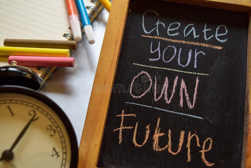 Δημιουργήστε το μέλλον σας ζωηρόχρωμο σε χειρόγραφο φράσης στον πίνακα κιμωλίας, το ξυπνητήρι με το κίνητρο και τις έννοιες εκπαί στοκ φωτογραφίες