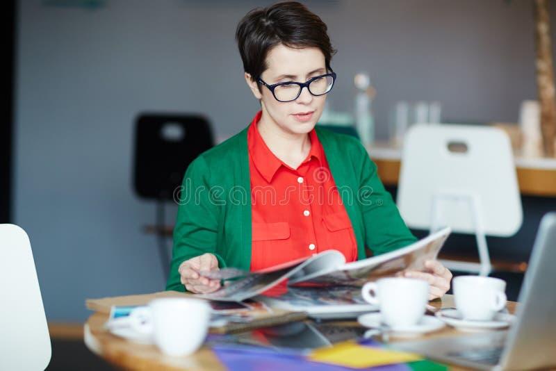 Δημιουργικά περιοδικά ανάγνωσης επιχειρηματιών στον καφέ στοκ εικόνα με δικαίωμα ελεύθερης χρήσης