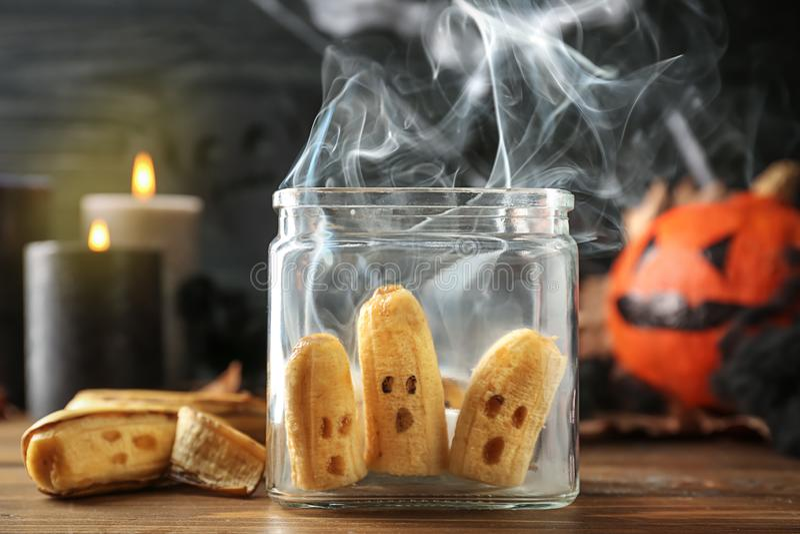 Δημιουργικές μπανάνες στο βάζο γυαλιού που προετοιμάζεται για το κόμμα αποκριών στον ξύλινο πίνακα στοκ εικόνα