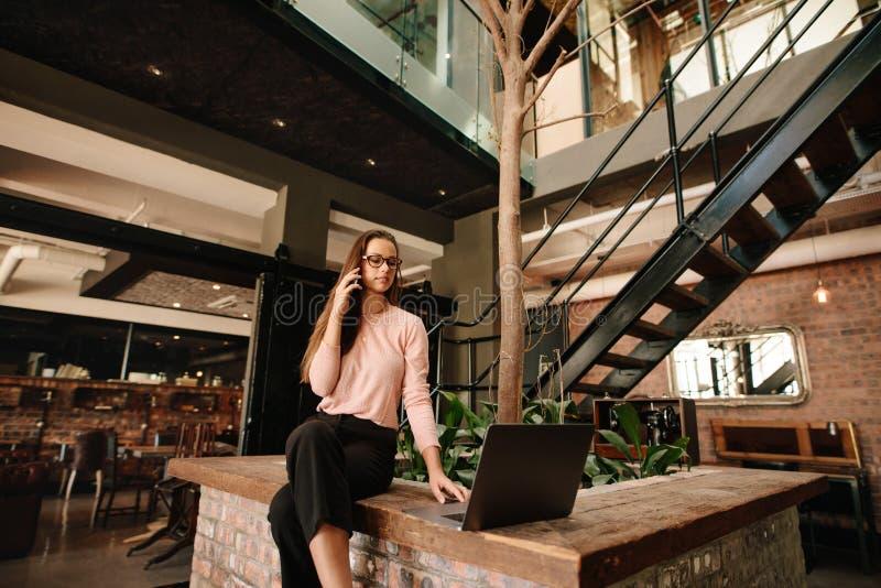 Δημιουργική γυναίκα στην καφετέρια με το lap-top και ομιλία στο τηλέφωνο στοκ φωτογραφία