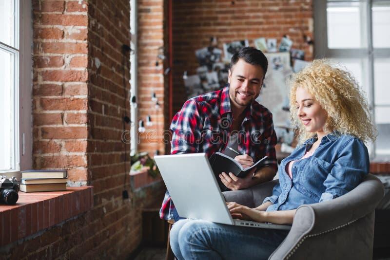 Δημιουργική διαδικασία με τη συμμετοχή ενός όμορφου άνδρα και μιας γυναίκας σε μια πολυθρόνα με ένα lap-top στοκ φωτογραφίες