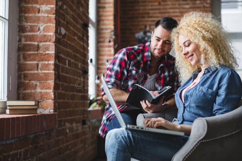 Δημιουργική διαδικασία με τη συμμετοχή ενός όμορφου άνδρα και μιας γυναίκας σε μια πολυθρόνα με ένα lap-top στοκ εικόνες