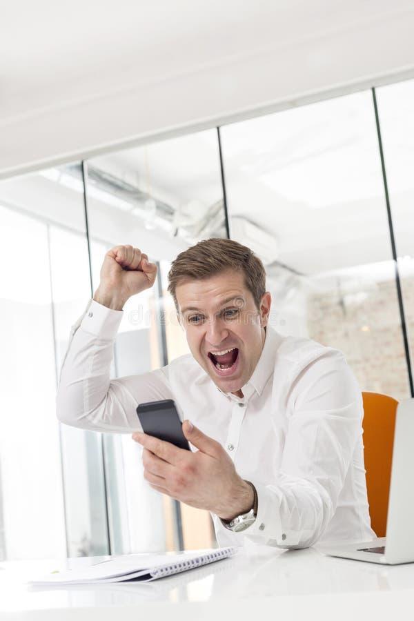 Δημιουργική επιτυχία εορτασμού επιχειρηματιών εξετάζοντας το smartphone στην αρχή στοκ φωτογραφία με δικαίωμα ελεύθερης χρήσης