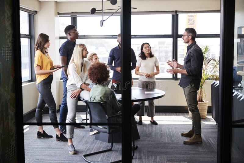Δημιουργική επιχειρησιακή ομάδα σε μια αίθουσα συνεδριάσεων που ακούει μια άτυπη παρουσίαση, που βλέπει από την πόρτα στοκ εικόνες