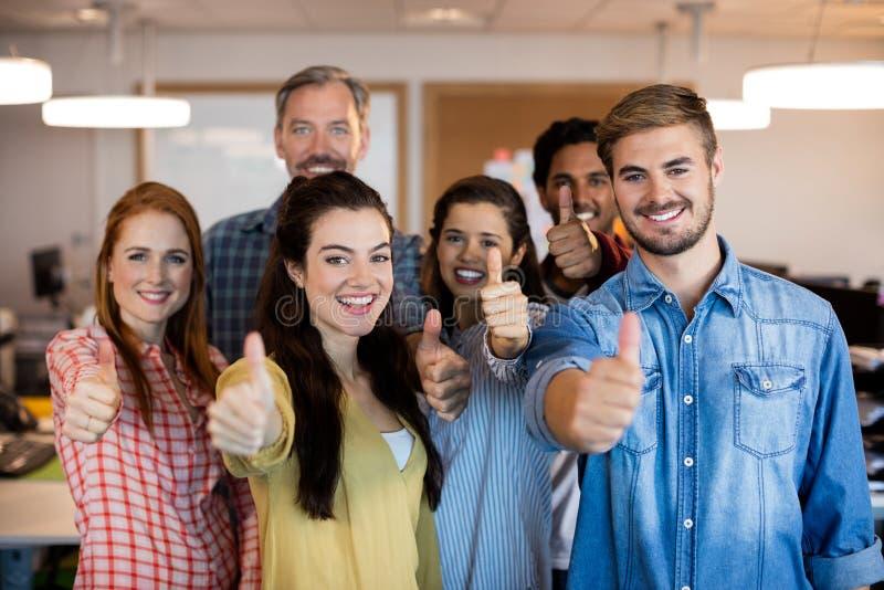 Δημιουργική επιχειρησιακή ομάδα που παρουσιάζει αντίχειρες στο γραφείο στοκ εικόνες