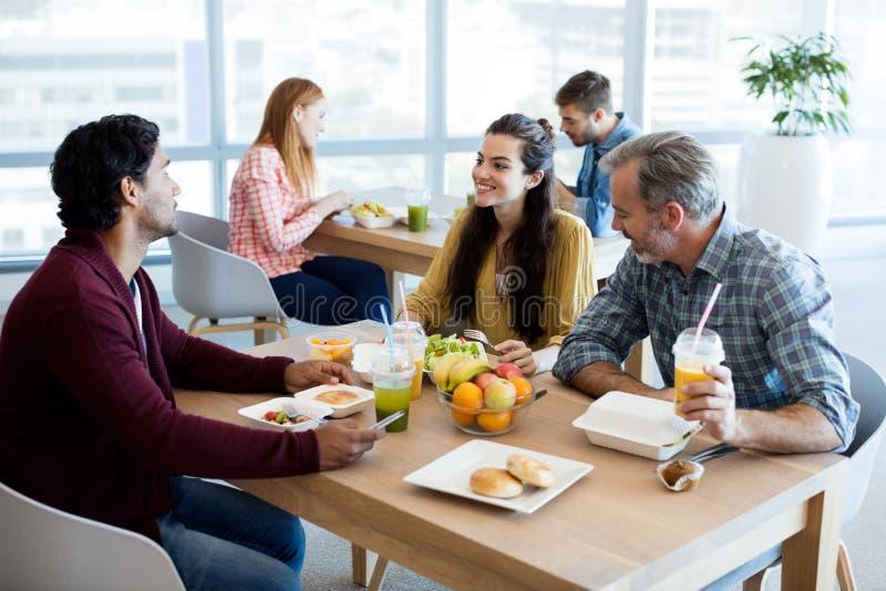 Δημιουργική επιχειρησιακή ομάδα που συζητά ενώ έχοντας το γεύμα στοκ φωτογραφία με δικαίωμα ελεύθερης χρήσης