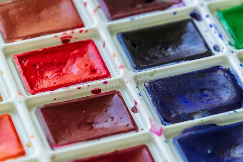 Δημιουργική καλλιτεχνική έννοια εκπαίδευσης - το κιβώτιο με το σύνολο ζωηρόχρωμου στενού επάνω χρωμάτων watercolor στοκ εικόνα