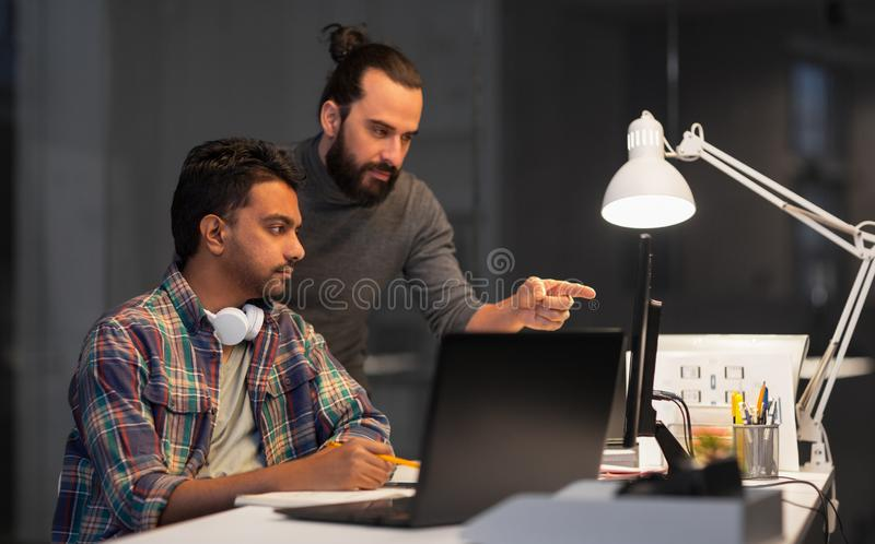 Δημιουργική ομάδα με τον υπολογιστή που λειτουργεί αργά στο γραφείο στοκ εικόνα