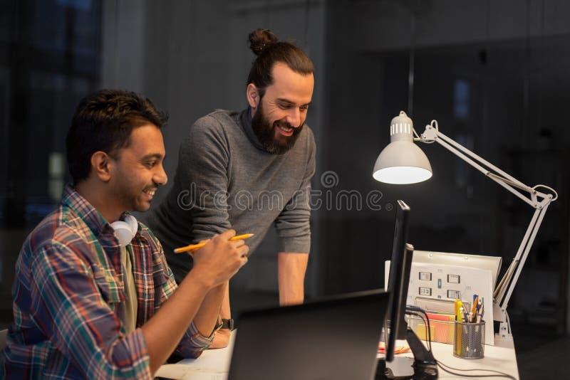 Δημιουργική ομάδα με τον υπολογιστή που λειτουργεί αργά στο γραφείο στοκ εικόνες