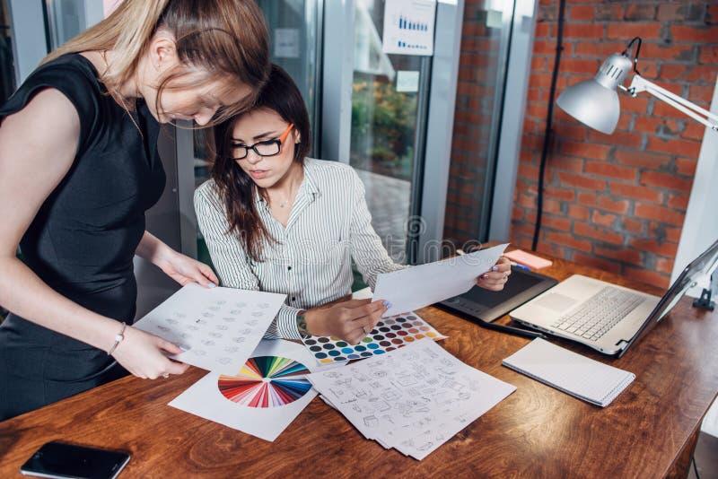 Δημιουργική ομάδα των γραφικών σχεδιαστών που εργάζονται στο νέο πρόγραμμα που χρησιμοποιεί swatches χρώματος και τα σκίτσα του σ στοκ εικόνα με δικαίωμα ελεύθερης χρήσης