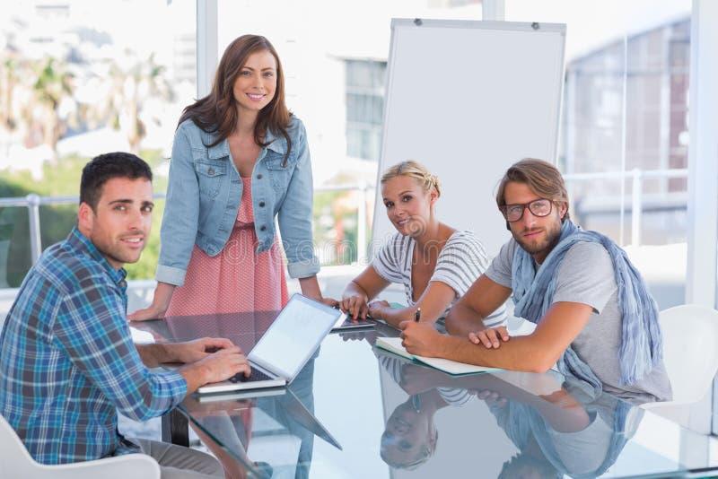 Δημιουργική ομάδα που διοργανώνει τη συνεδρίαση και που χαμογελά στη κάμερα στοκ εικόνα
