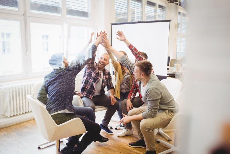 Δημιουργικοί επιχειρηματίες που δίνουν υψηλός-πέντε στην αίθουσα συνεδριάσεων στοκ εικόνα με δικαίωμα ελεύθερης χρήσης