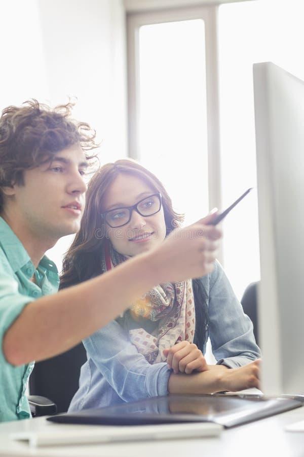 Δημιουργικοί επιχειρησιακοί συνάδελφοι που συζητούν πέρα από τον υπολογιστή γραφείου στην αρχή στοκ εικόνες