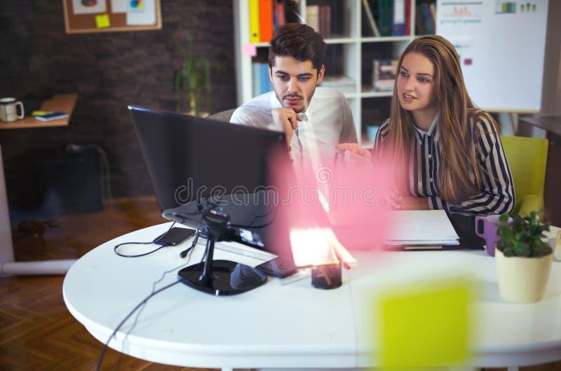 Δημιουργικοί επιχειρησιακοί συνάδελφοι που χρησιμοποιούν τον υπολογιστή γραφείου στην αρχή στοκ εικόνα με δικαίωμα ελεύθερης χρήσης