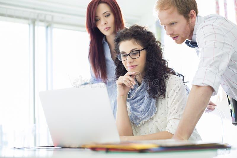 Δημιουργικοί επιχειρησιακοί συνάδελφοι που χρησιμοποιούν το lap-top στο γραφείο στην αρχή στοκ εικόνες με δικαίωμα ελεύθερης χρήσης