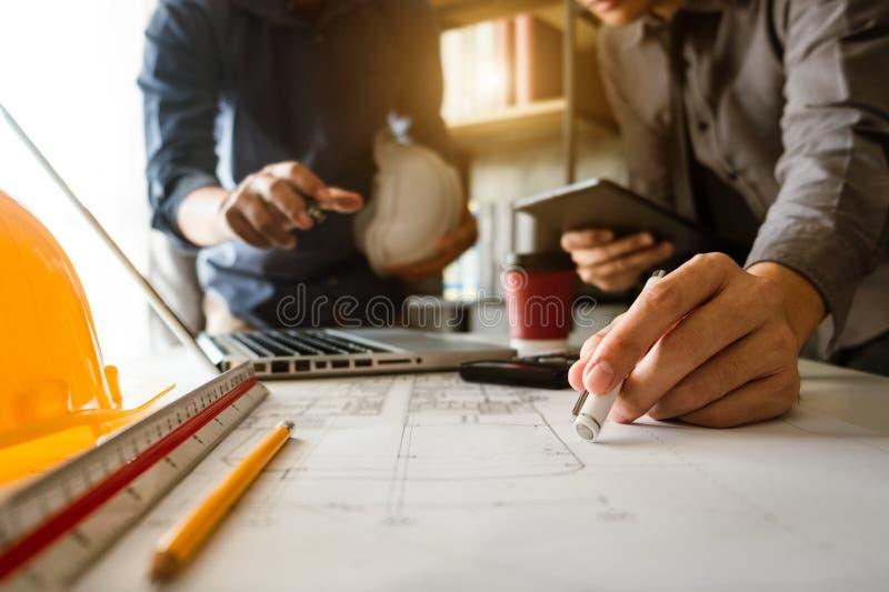 Δημιουργικός αρχιτέκτονας που προβάλλει στα μεγάλα σχέδια στο σκοτεινό γραφείο σοφιτών στοκ εικόνες