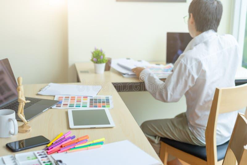 Δημιουργικός γραφικός λειτουργώντας υπολογιστής γραφείου σχεδίου, αρχιτέκτονες που επιλέγει τα δείγματα χρώματος στοκ εικόνες