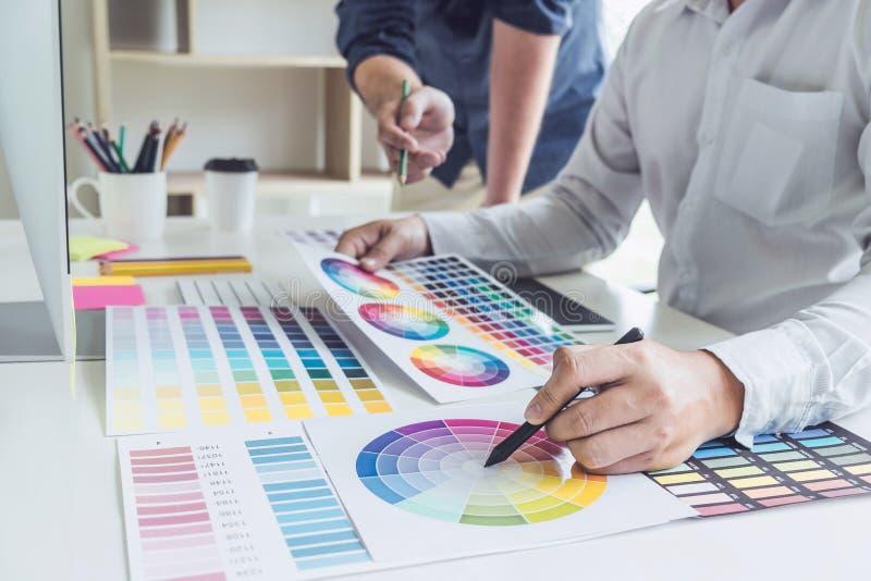 Δημιουργικός γραφικός σχεδιαστής δύο συναδέλφων που εργάζεται στην επιλογή χρώματος και που επισύρει την προσοχή στην ταμπλέτα γρ στοκ φωτογραφίες με δικαίωμα ελεύθερης χρήσης
