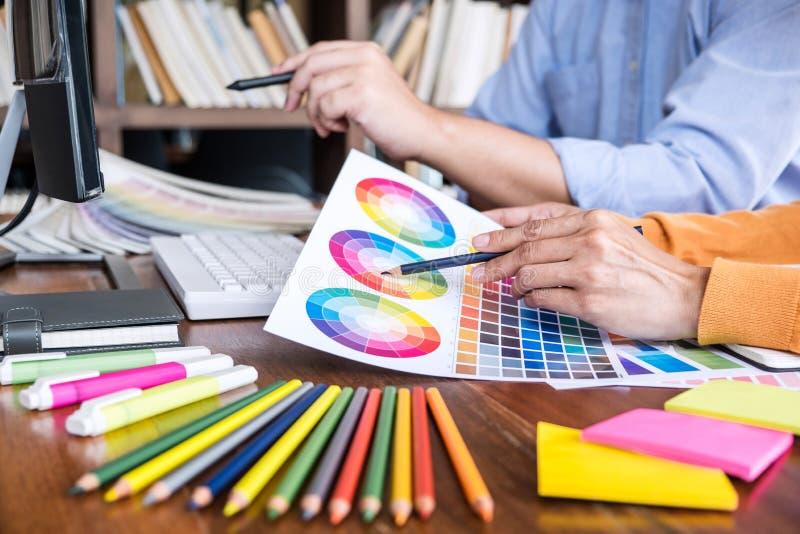 Δημιουργικός γραφικός σχεδιαστής δύο συναδέλφων που εργάζεται στο χρώμα επίλεκτο στοκ εικόνες