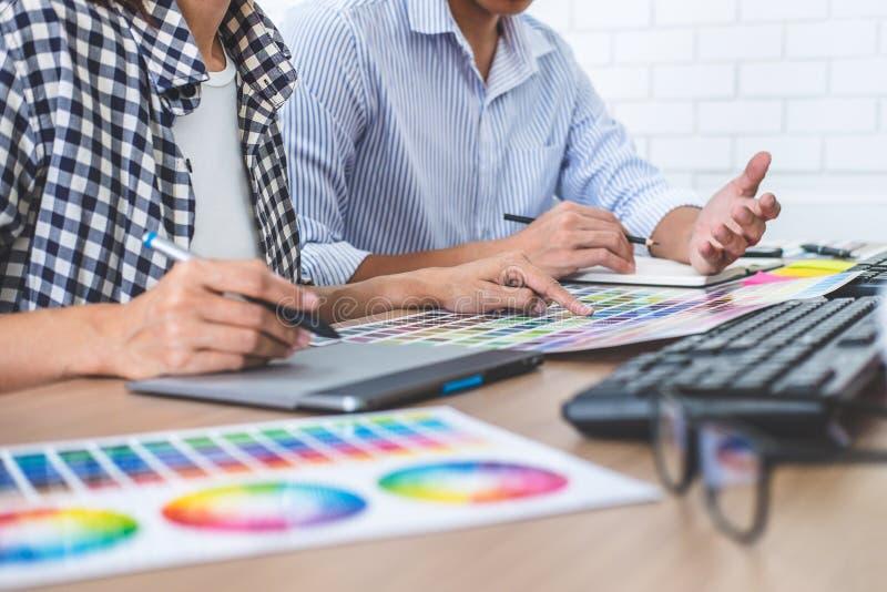 Δημιουργικός γραφικός σχεδιαστής δύο συναδέλφων που εργάζεται στο χρώμα επίλεκτο στοκ φωτογραφία